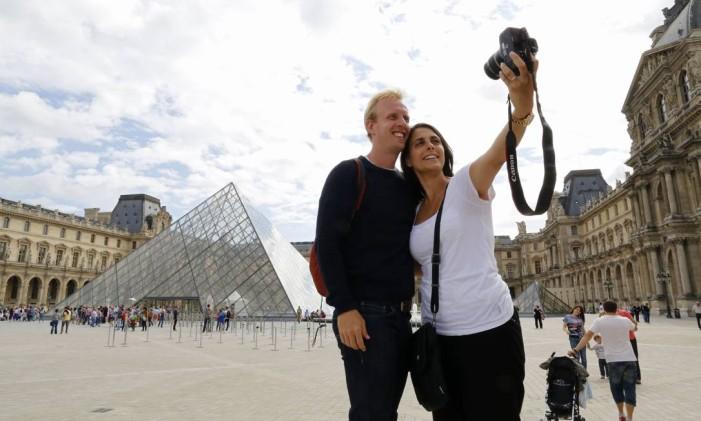 Turistas diante da pirâmide do museu do Louvre, em Paris. Foto: Jacky Naegelen / Reuters