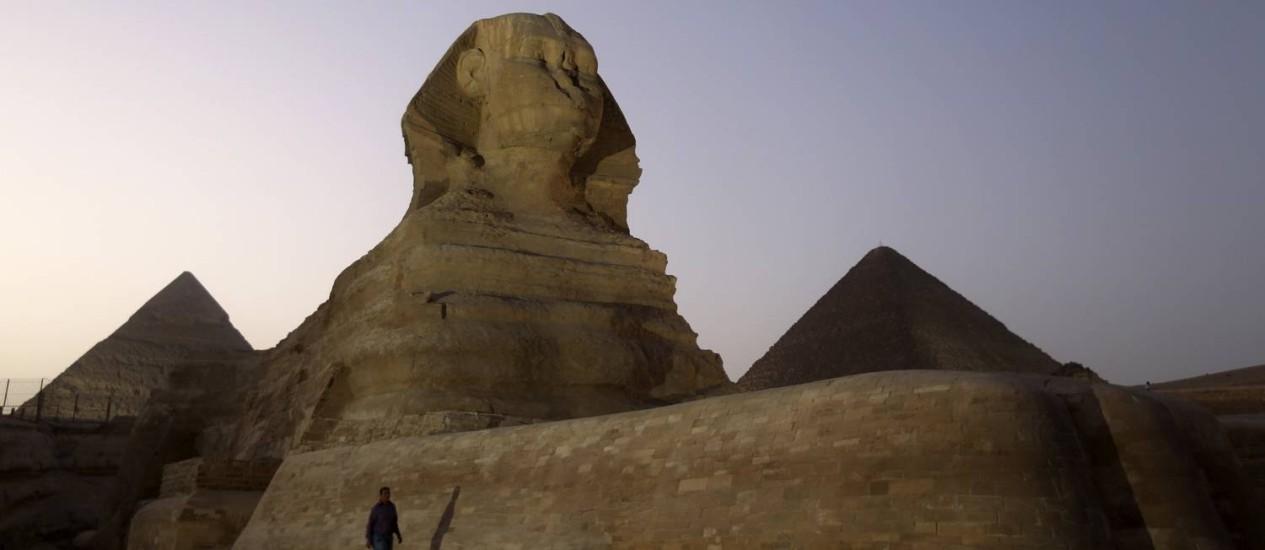 Homem caminha ao lado na Grande Esfinge de Gizé, entre as pirâmides Miquerinos (direita) e Quéfren (esqueda) Foto: MOHAMED ABD EL GHANY / REUTERS