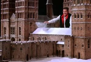 Um dos artistas penera uma mistura de sal com papel picado sobre o castelo Foto: Divulgação