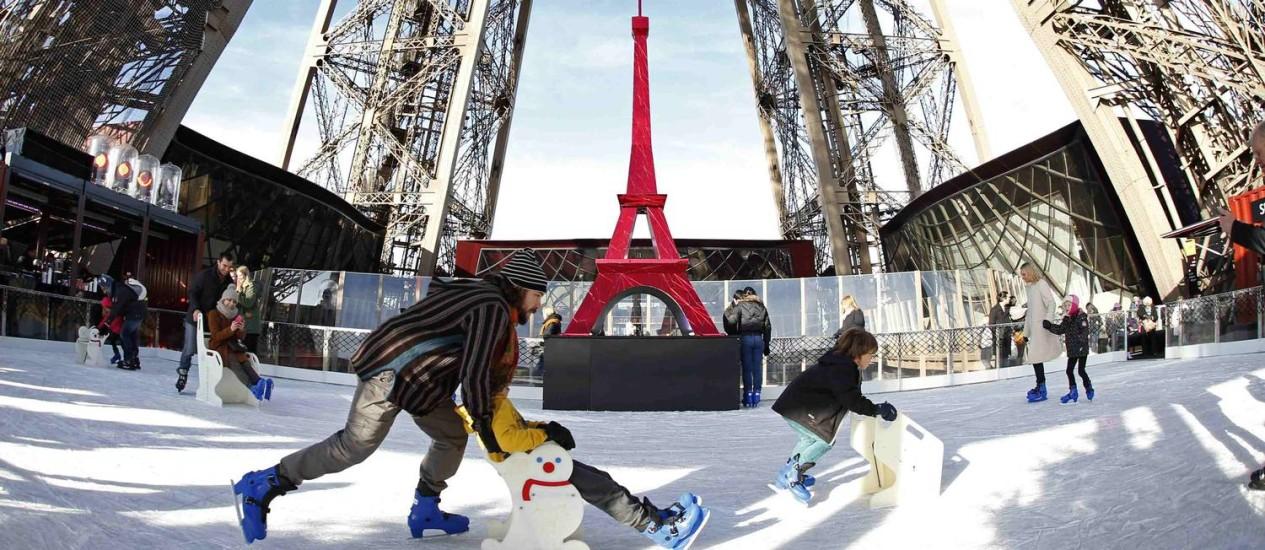 Turistas patinam na pista montada no primeiro andar da Torre Eiffel Foto: CHARLES PLATIAU / REUTERS