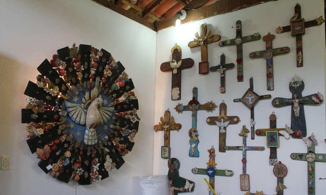 Crucifixos e Divinos adornam as paredes da Oficina de Agosto; a maioria da peças é feita com madeira de demolição Foto: Agência O Globo / Ana Beatriz Marin