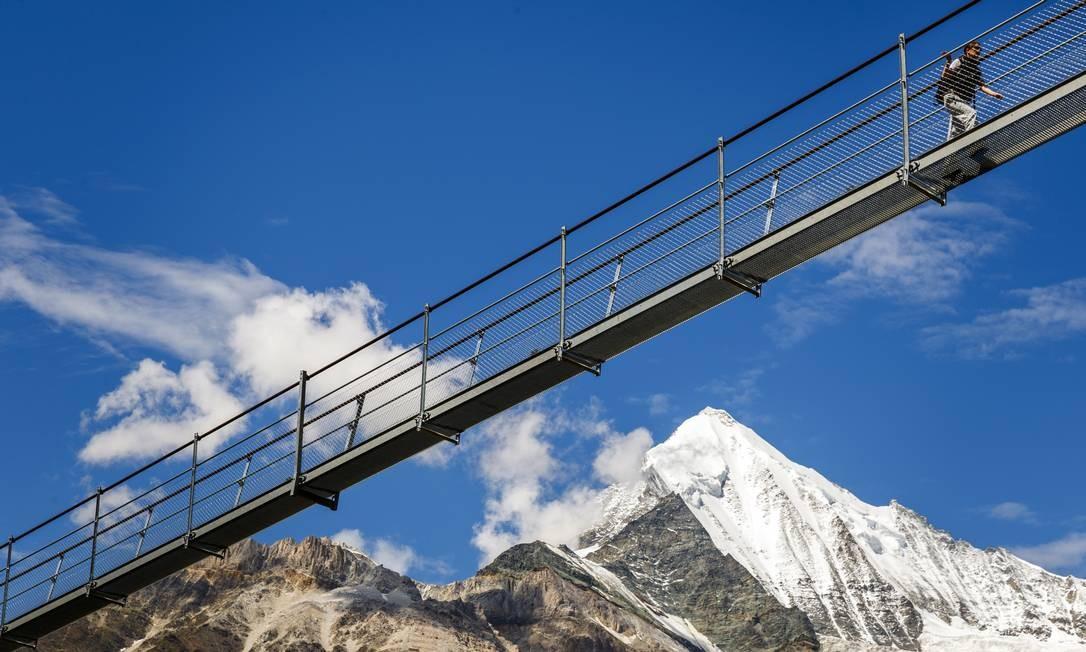 Uma pessoa passa pela Europabruecke, supostamente a mais longa ponte suspensa de pedestres, com 494m, inaugurada em 29 de julho, em Randa, na Suíça, entre as vilas de Zermatt e Graechen Foto: Valentin Flauraud/Keystone / AP