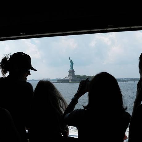 Do Staten Island ferry, passageiros observam a Estátua da Liberdade, em Nova York Foto: SPENCER PLATT / AFP/3-8-2017