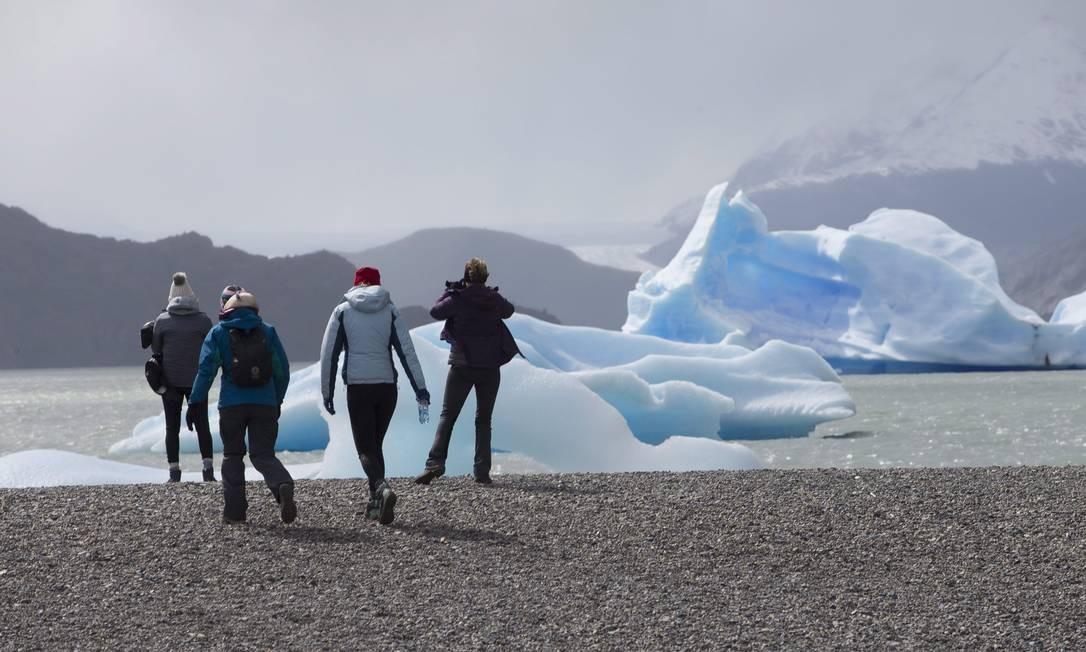 Turistas caminham às margens do Lago Grey, onde flutuam enormes pedaços de gelo que se desprendem das montanhas, no Parque Nacional Torres del Paine Foto: Edilson Dantas / Agência O Globo