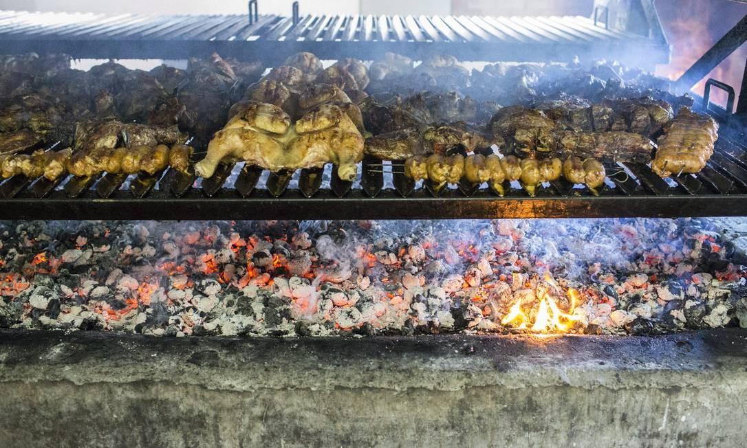 Na parrilla. Almoço preparado no Parque Nacional Bernardo O'Higgins inclui cordeiro assado, frango, linguiça tipica da região, batatas e salada Foto: Edilson Dantas / Agência O Globo