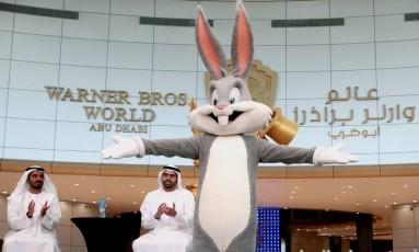Diversão. Mohamed Khalifa Al Mubarak (à direita), Presidente da Autoridade de Turismo e Cultura de Abu Dhabi, aplaude Pernalonga na apresentação do Parque da Warner Bros Foto: CHRISTOPHER PIKE / REUTERS
