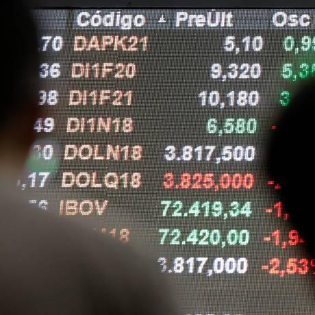 Em São Paulo, pessoas observam painel eletrônico mostranto a flutuação do câmbio com os valores de negociação do dólar em relação ao real Foto: PAULO WHITAKER / REUTERS/8-6-2018
