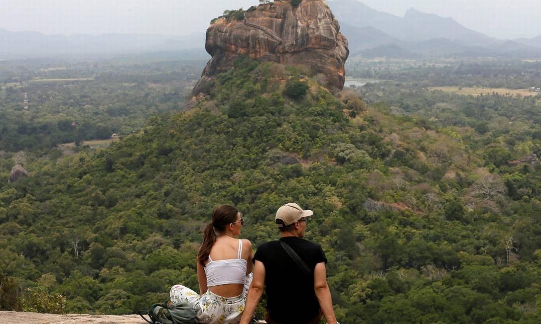 Casal observa a paisagem dominada pela fortaleza de Sigiriya Rock, também conhecida como Rocha do Leão, patrimônio mundial preservado pela Unesco no Sri Lanka Foto: DINUKA LIYANAWATTE / REUTERS