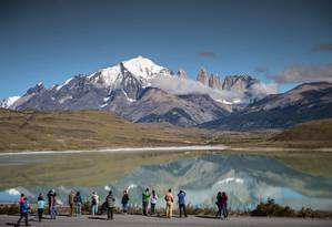 Turistas fotografam os picos de Torres del Paine, a quase dois mil quilômetros ao sul de Santiago, no parque nacional que faz parte da Rota dos Parques da Patagônia, no Chile Foto: MARTIN BERNETTI / AFP/26-2-2016