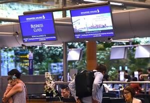 Funcionários da Singapore Airlines atendem passageiros durante os procedimentos de check-in para o voo inaugural SQ22 para Newark (NJ), EUA, no Changi International Airport em Cingapura Foto: ROSLAN RAHMAN / AFP