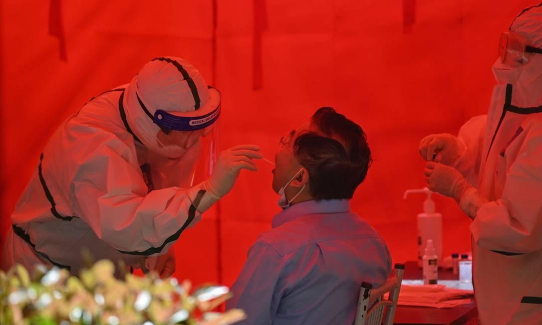 Profissional da saúde testa homem para o Covid-19 em Wuhan, marco zero da pandemia, onde as autoridades ordenaram que todos os 11 milhões de moradores sejam testados para a doença Foto: HECTOR RETAMAL / AFP / 19-05-2020