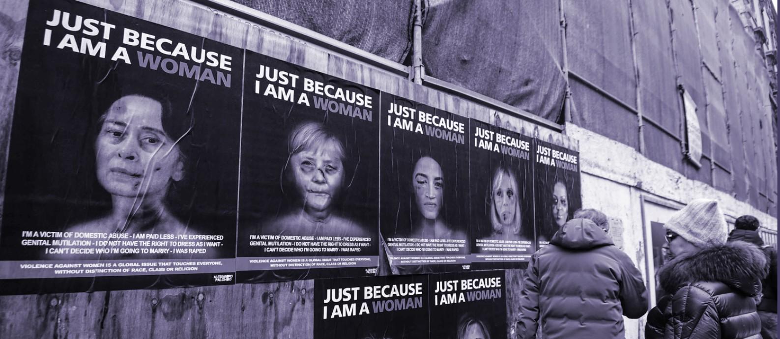 Em Milão, pedestres para para ler cartazes feitos pelo artista Alexsandro Palombo com imagens de mulheres protagonistas da política internacional retratadas como vítimas de agressão Foto: AFP