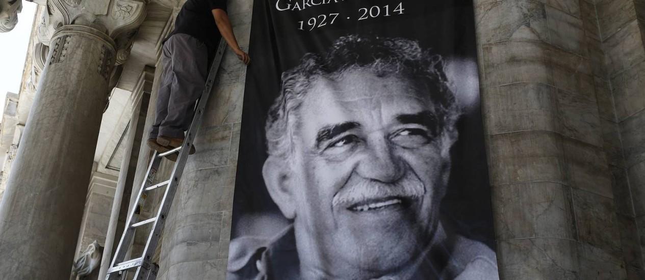 Homem coloca cartaz de Gabriel García Márquez na parede do Palácio de Belas Artes, no México Foto: TOMAS BRAVO / REUTERS