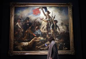 Mulher observa 'La liberte guidant le peuple', no Louvre Foto: Christophe Ena / AP