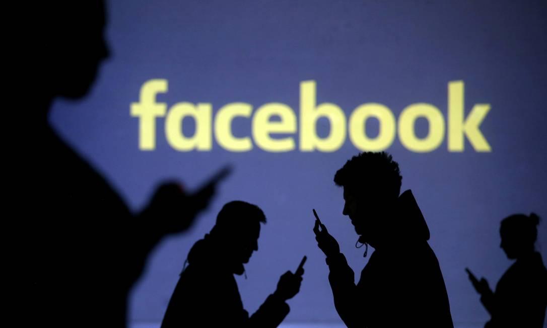 Usuários mexem no celular em frente a uma projeção com o logo do Facebook Foto: Dado Ruvic / REUTERS
