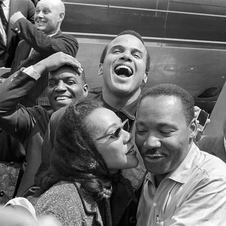 Nessa imagem de 1963, antes da depressão, Martin Luther King, Jr. recebe um beijo da mulher, Coretta Scott King, ao chegar em Alabama com os amiguis e ativistas Nipsey Russell (à esquerda) e Harry Belafonte (centro, rindo) Foto: Divulgação