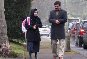 A paquistanesa Malala Yousafzai, prêmio Nobel da Paz, caminha com seu pai, Ziauddin, em Birmingham, na Inglaterra Foto: LIZ CAVE / AFP