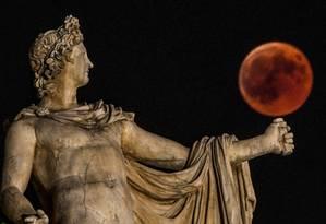 A lua cheia, durante eclipse, atrás da estátua de Apolo, em Atenas, em 2018 Foto: ARIS MESSINIS/AFP