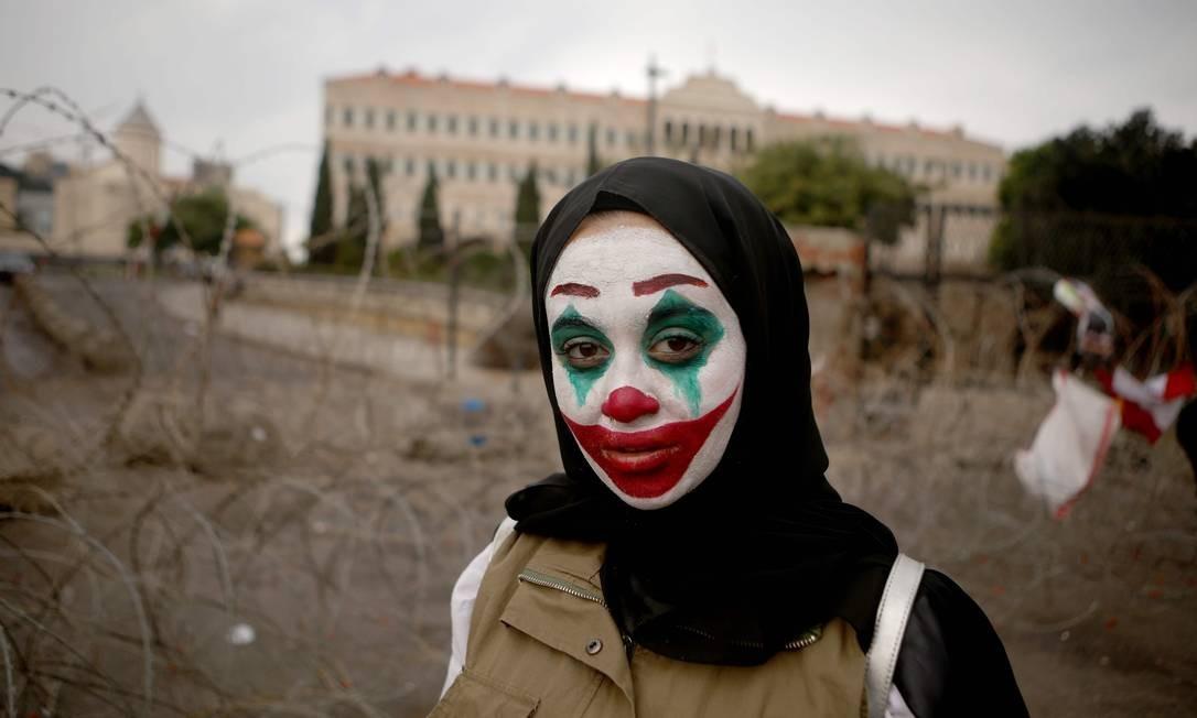 Libanesa se caracteriza como Coringa durante protesto em Beirute Foto: PATRICK BAZ / AFP