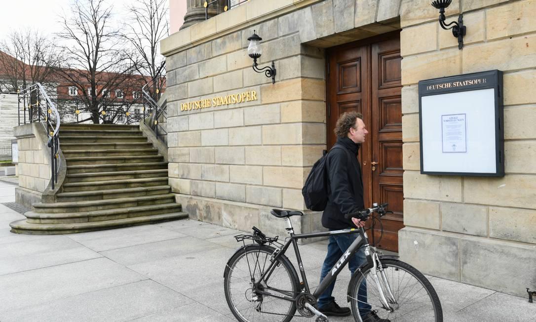 Um homem lê o cartaz que informa a interrupção da agenda do Berlin State Opera, devido ao coronavírus Foto: ANNEGRET HILSE / REUTERS