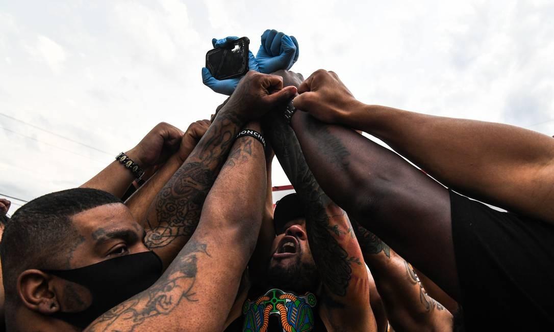 Pessoas levantam as mãos e se ajoelham enquanto protestam no memorial improvisado em homenagem a George Floyd, nesta terça-feira, em Minneapolis, Minnesota, EUA Foto: CHANDAN KHANNA / AFP