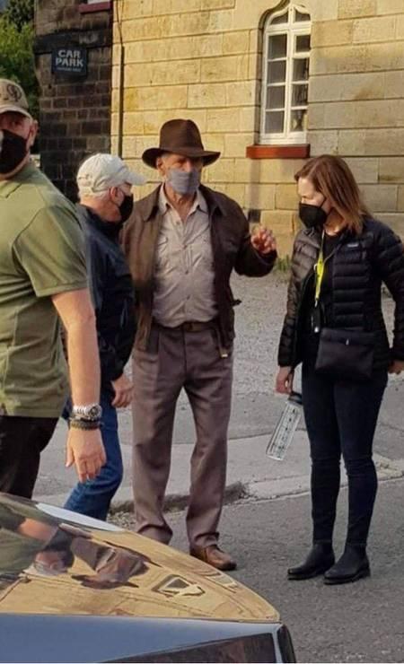 Harrison Ford conversa com a produtora Kathleen Kennedy e o marido dela, o também produtor Frank Marshall, no set de filmagens de 'Indiana Jones 5', no Reino Unido Foto: Twitter / Reprodução