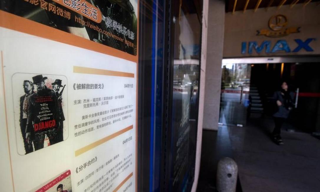 Mulher passa por cinema em Pequim nesta quinta-feira, onde pôster promove a estreia de 'Django livre' Foto: Andy Wong / AP