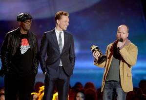 Atores Samuel L. Jackson e Tom Hiddleston com o diretor Joss Whedon no palco ao vencerem o prêmio de Filme do Ano por 'Os Vingadores' Foto: KEVORK DJANSEZIAN / AFP
