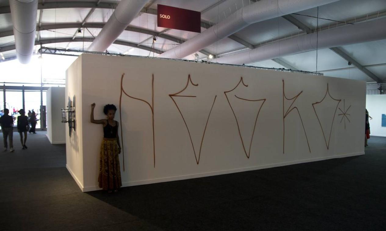 Grafite numa parede da feira: intervenção discute segregação do negro no mercado de arte Foto: Antonio Scorza / Agência O Globo