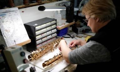 Funcionária monta saxofone na fábrica da Selmer em Mantes-la-Ville, França. Foto: Benoit Tessier / Reuters