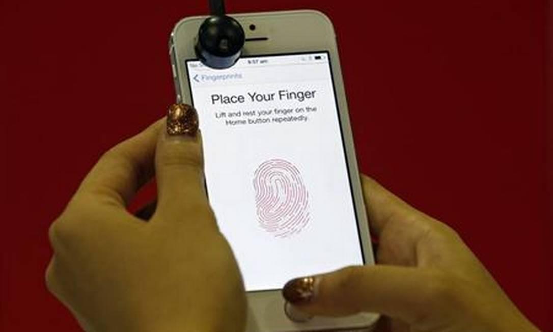Demonstradora apresenta scanner de impressões digitais do iPhone 5S em Cingapura, em 20 de setembro de 2013 Foto: Edgar Su / Reuters / Edgar Su / Reuters
