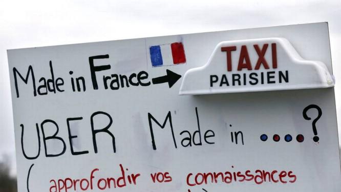 """""""Taxi parisiense é made in France. E o Uber, é made in...? Vamos aprofundar nossas relações"""", diz cartaz em manifestação parisiense contra o Uber Foto: Bloomberg"""