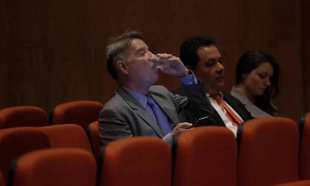 Mais uma vez com o celular na mão, Eike Batista bebe água durante a audiência na Justiça Federal do Rio por manipulação de mercado e informação privilegiada Foto: Alexandre Cassiano / Agência O Globo