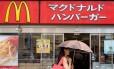 Mulher passa em frente a uma loja do McDonald's em Tóquio