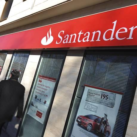 Homem caminha em frente a uma agência do banco Santander em Madri Foto: Simon Dawson / Bloomberg