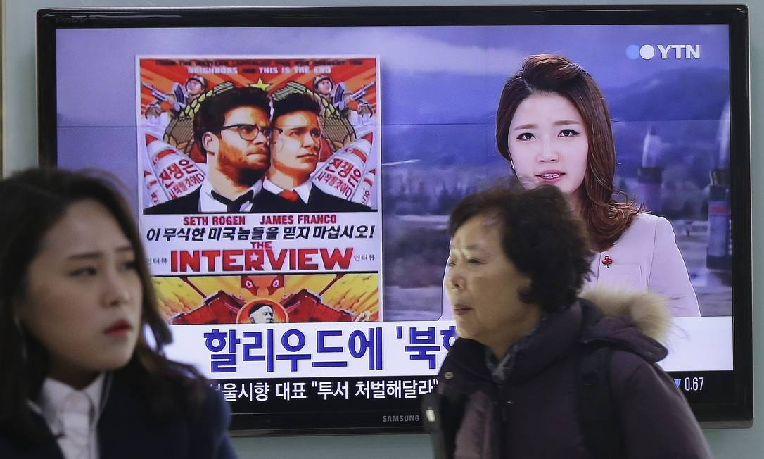 """People walk past a TV screen showing a poster of Sony Picture's """"The Interview"""" in a news report, at the Seoul Railway Station in Seoul, South Korea, Monday, Dec. 22, 2014. North Korea hates the Hollywood film that revolves around the assassination of its beloved leader, but the country has had a long love affair with cinema - of its own particular styling. The Korean letters on the screen read """" Hollywood"""". (AP Photo/Ahn Young-joon) Foto: Ahn Young-joon / AP"""