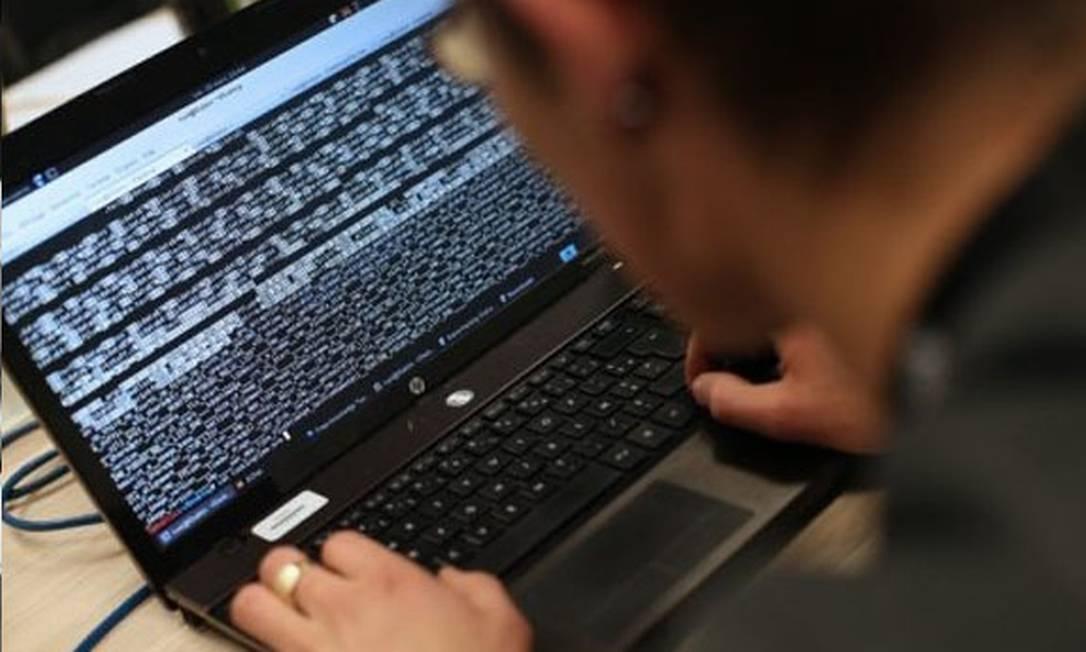 Hacker em ação analisando dump de memória em laptop Foto: AFP