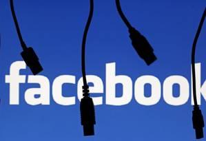Cabos eletrônicos aparecem em silhueta ante a logo do Facebook em 23 de setembro de 2014 em Saraievo, na Bósnia e Herzegovina Foto: Dado Ruvic / REUTERS