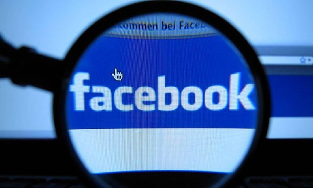 Logo do Facebook visto por lente de aumento Foto: Jörg Koch / AP Photo