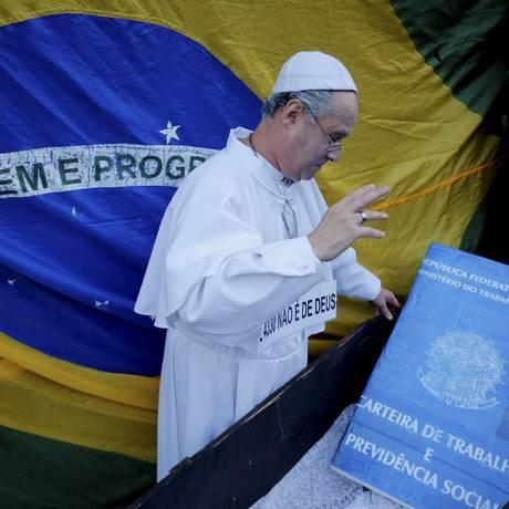 Vestido como o Papa, manifestante dá 'extrema unção' à carteira de trabalho Foto: Marcelo Piu / Agência O Globo
