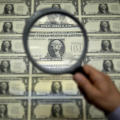 Inspeção de notas de dólar Foto: Andrew Harrer / Bloomberg News