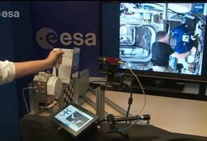 À esquerda, a mão de André Schiele, na Terra; e na tela, Terry Virts em alavanca semelhante, na ISS Foto: Reprodução / YouTube