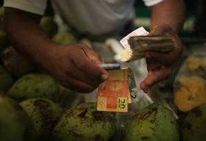 Vendedor conta notas de real em uma feira livre do Rio Foto: Dado Galdieri / Bloomberg