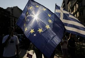 Manifestantes estendem bandeiras da União Europeia e da Grécia durante protestos, nesta quinta-feira, em Thessaloniki, contra e a favor da permanência do país na zona do euro Foto: Konstantinos Tsakalidis / Bloomberg
