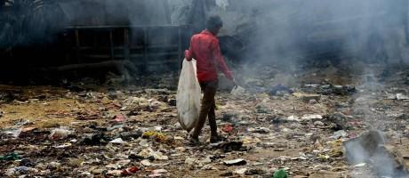 Indiano caminho em meio a lixo queimado Foto: MONEY SHARMA / AFP