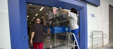 Cliente entra em agência da Caixa enquanto funcionária retira adesivo de greve Foto: Márcia Foletto/Agência O Globo