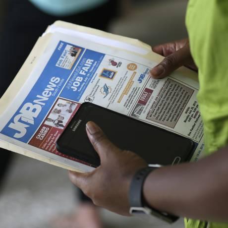 Mulher carrega jornal com ofertas de emprego no EUA Foto: Lynne Sladky / AP