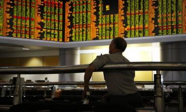 Malaio observa o desempenho do mercado financeiro em Kuala Lumpur Foto: Lim Huey Teng / AP