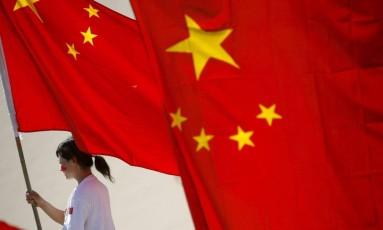 Mulher levando bandeira da China Foto: Oliver Weiken / EFE