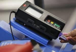 Consumidor usa cartão para compra Foto: Patrick T. Fallon / Bloomberg